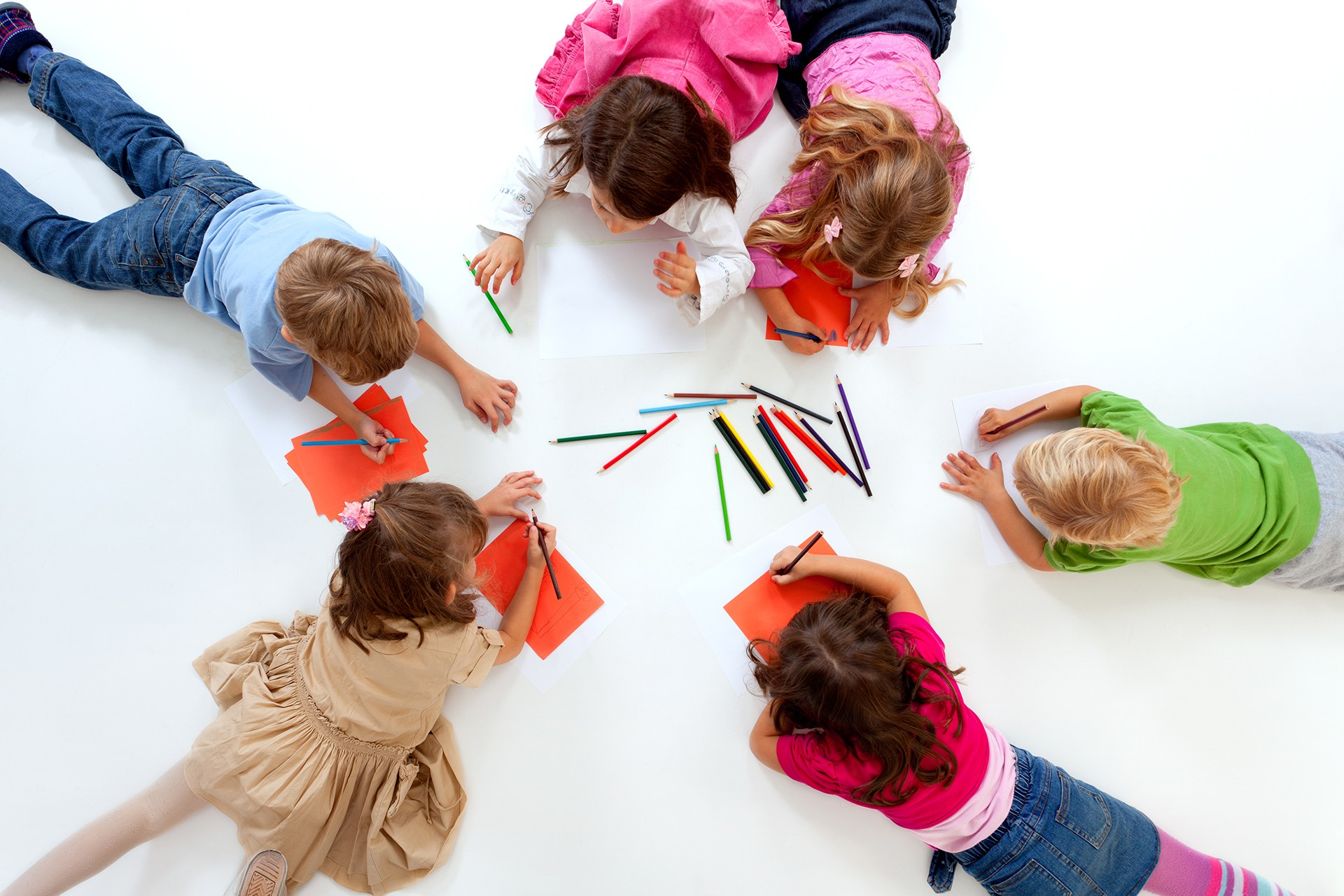 Happy group of children lying down in circle and drawing